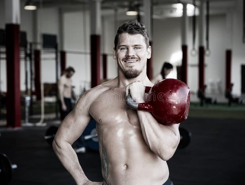Gymnase musculaire de Holding Kettlebell In d'entraîneur photos stock