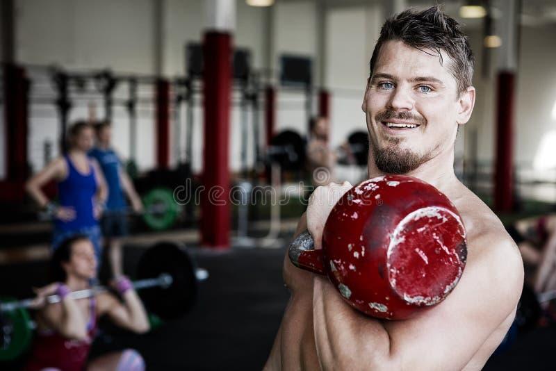 Gymnase musculaire de Lifting Kettlebell In d'entraîneur photos stock