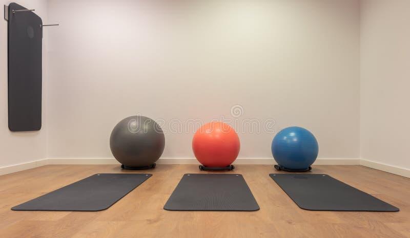 Gymnase pour des exercices de forme physique Fitball et mensonge de tapis sur le plancher en bois Forme physique, sport, formatio images libres de droits