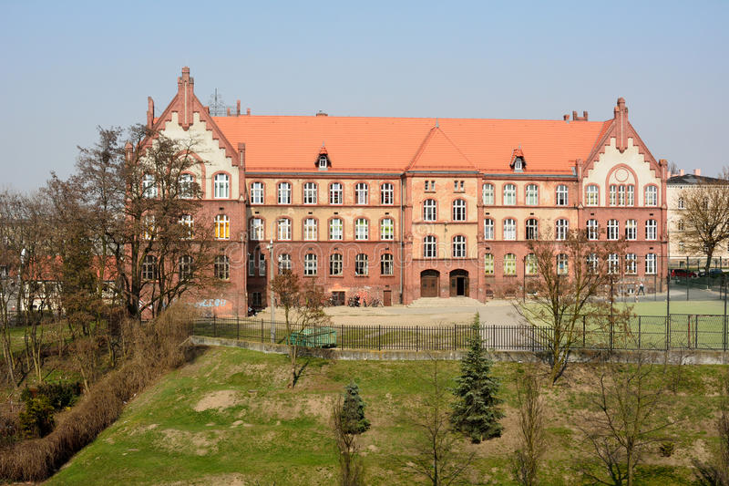 Gymnasium No. 1 in Gniezno, Poland. Gniezno, Poland – April 5, 2016. Gymnasium No. 1 in Gniezno, Poland with grass lawn, trees and people royalty free stock photo