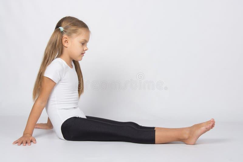 Gymnast κοριτσιών η συνεδρίαση στο πάτωμα και εξετάζει την τα πόδια στοκ φωτογραφίες με δικαίωμα ελεύθερης χρήσης