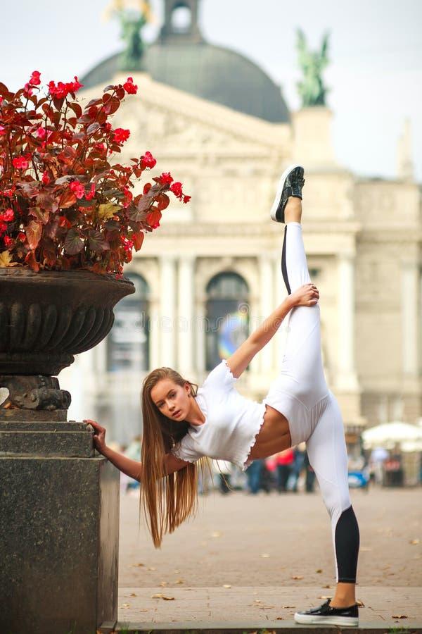 Gymnast κοριτσιών που κάνει την τεντώνοντας άσκηση στο τετράγωνο της πόλης τουριστών στοκ εικόνα με δικαίωμα ελεύθερης χρήσης