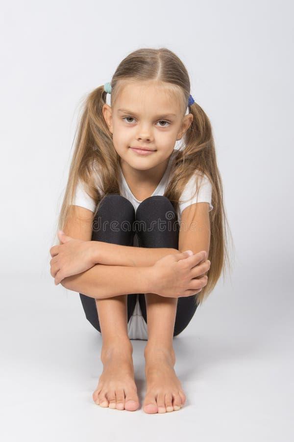 Gymnast κοριτσιών συνεδρίαση στο πάτωμα που αγκαλιάζει τα πόδια του στοκ φωτογραφίες