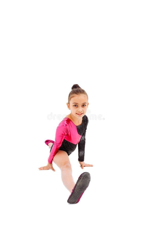 Gymnast μικρών κοριτσιών συνεδρίαση στις διασπάσεις Απομονωμένος στο λευκό στοκ εικόνες