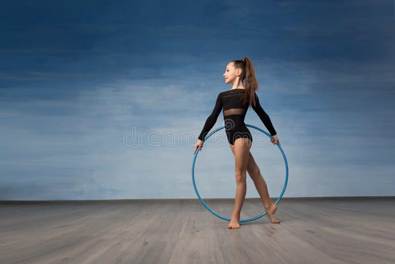 Gymnast νέων κοριτσιών σε ένα μαύρο κοστούμι λουσίματος κοιτάζει στο σχεδιάγραμμα στα χέρια μιας γυμναστικής στεφάνης στοκ φωτογραφία με δικαίωμα ελεύθερης χρήσης