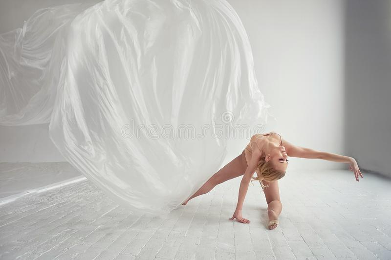 Gymnast που χορεύει με μια διαφανή ταινία σε έναν άσπρους τοίχο και ένα πάτωμα Grace και υγιής τρόπος ζωής στοκ φωτογραφίες με δικαίωμα ελεύθερης χρήσης