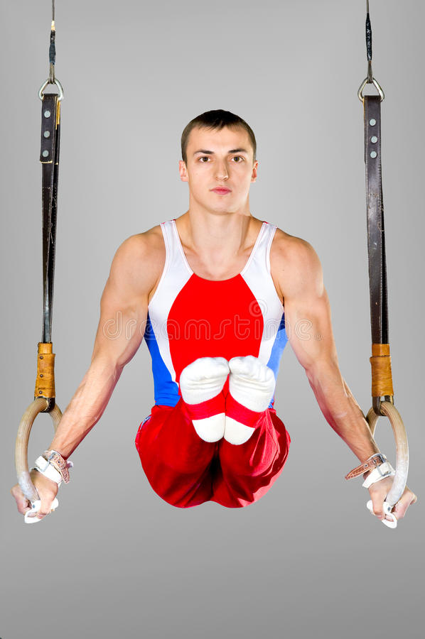 Gymnast. The sportsman the guy, carries out difficult exercise, sports gymnastics stock images