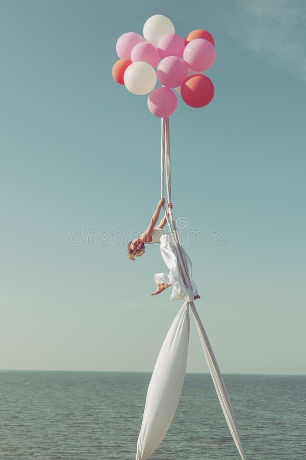 Gymnast on balls in the sky. Woman gymnast flies on balls high in the sky she shows performance stock image