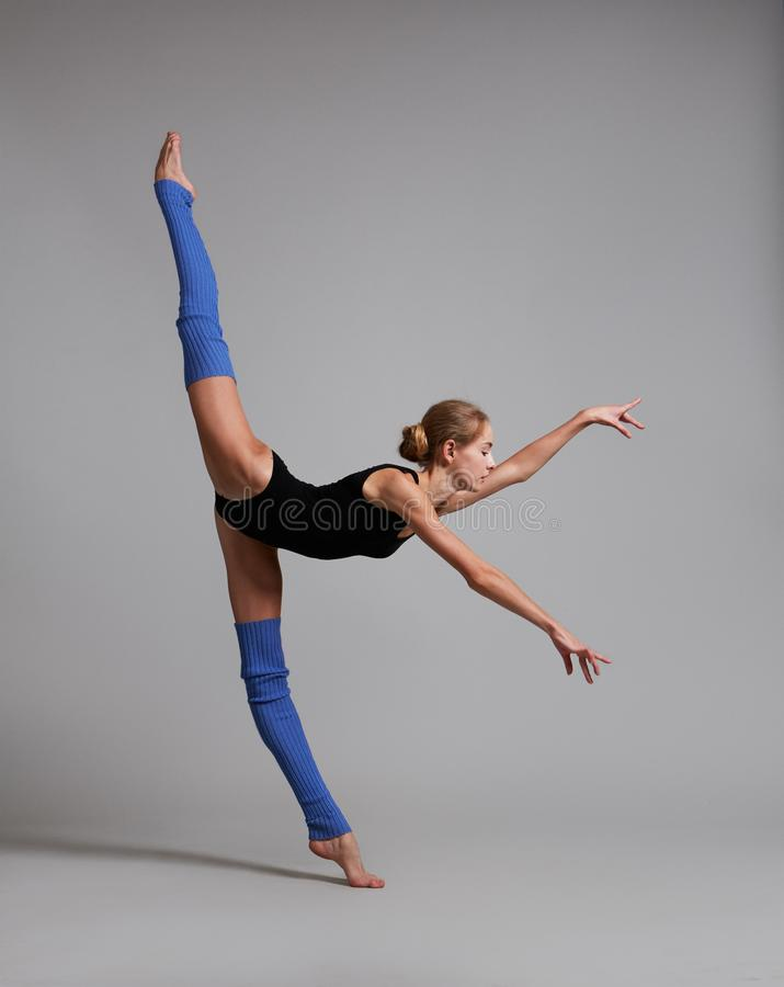 Gymnast doing vertical split. Color photo. Gymnast in black lingerie and royalty free stock image