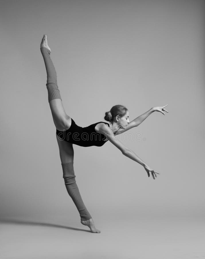 Gymnast doing vertical split. Black and white photo. Gymnast in black lingerie and royalty free stock photo