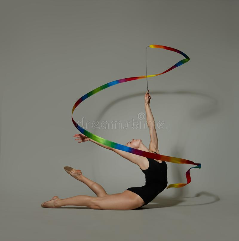 Gymnast with a ribbon  deflection back. Gymnast in black lingerie with a ribbon stock photography