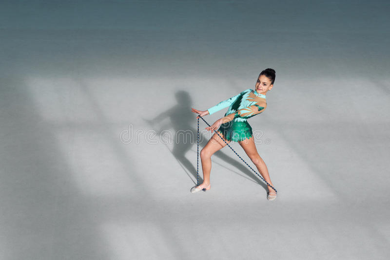Gymnast in costume performs exercises with rope royalty free stock images