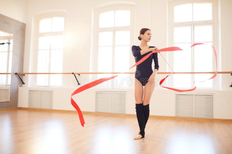 Gymnast dancing with ribbon. Concentrated attractive young female rhythmic gymnast in black bodysuit dancing with red ribbon while preparing for competition royalty free stock images
