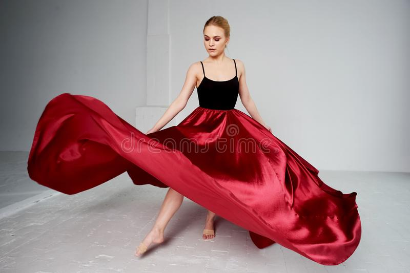 A gymnast in a dark top and a red silk skirt. The color of passion, of aggression.Tango. Plastic body, airiness. A gymnast in a dark top and a red silk skirt stock photo