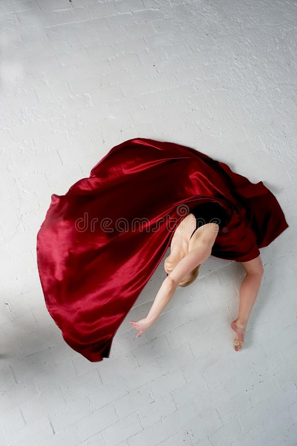 A gymnast in a dark top and a red silk skirt. The color of passion, of aggression.Tango. Plastic body, airiness. A gymnast in a dark top and a red silk skirt stock images