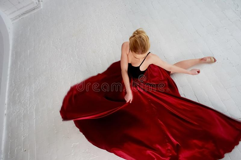 A gymnast in a dark top and a red silk skirt. The color of passion, of aggression.Tango. Plastic body, airiness. A gymnast in a dark top and a red silk skirt royalty free stock photos
