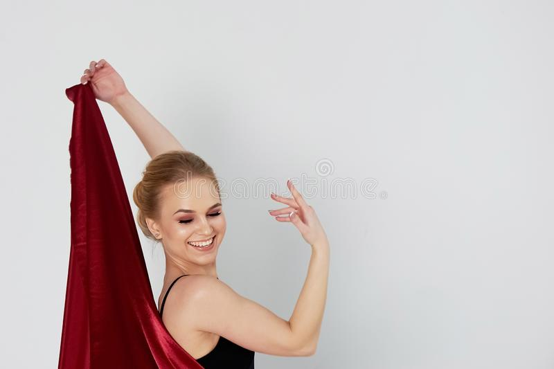 A gymnast in a dark top and a red silk skirt. The color of passion, of aggression.Tango. Plastic body, airiness. A gymnast in a dark top and a red silk skirt royalty free stock images