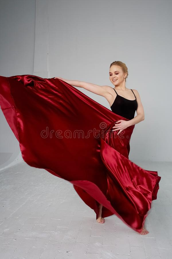 A gymnast in a dark top and a red silk skirt. The color of passion, of aggression.Tango. Plastic body, airiness. A gymnast in a dark top and a red silk skirt stock image