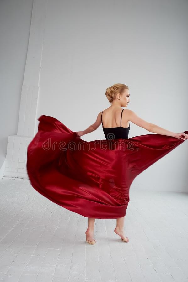 A gymnast in a dark top and a red silk skirt. The color of passion, of aggression.Tango. Plastic body, airiness. A gymnast in a dark top and a red silk skirt royalty free stock photography