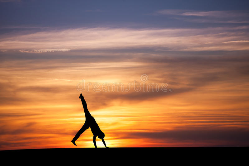 Gymnast doing cartwheel in sunset. Silhouetted gymnast doing cartwheel in sunset royalty free stock images