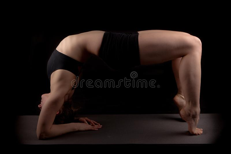 Gymnast elbows toes backward bend. Girl in gymnast outfit standing on her elbows and toes facing upward on a black background royalty free stock photos