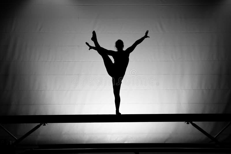 Gymnast fêmea no feixe de balanço imagens de stock