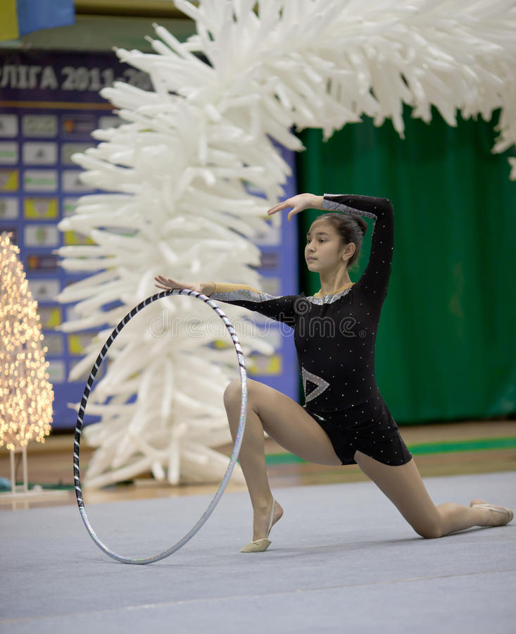 Gymnast girl doing exercise with hoola hoop. Girl doing exercice with hoola hoop. Gimnastics open tournament. 16-17th December 2011, Lviv, Ukraine royalty free stock photography