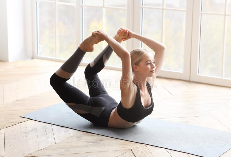 Gymnast girl exercising in studio, laying on yoga mat royalty free stock images