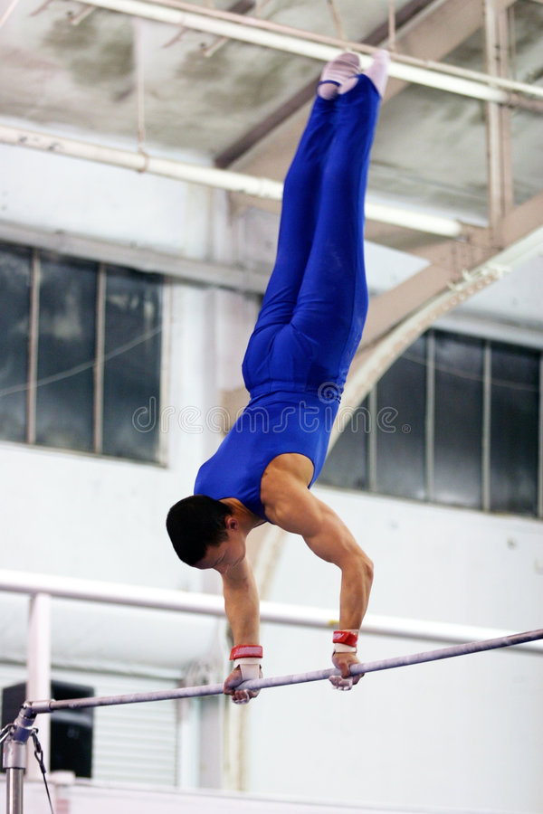 Gymnast na barra elevada fotografia de stock