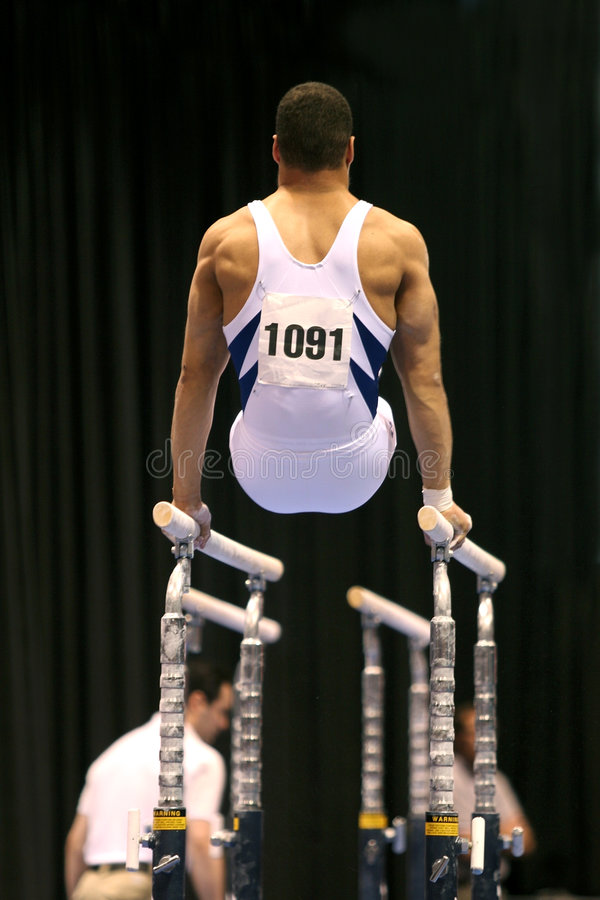 Gymnast on parallel bars stock photos