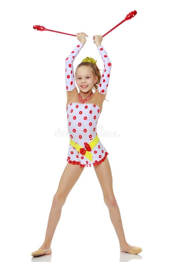 Gymnast κοριτσιών εκτελεί τις ασκήσεις με μια ράβδο στοκ εικόνα