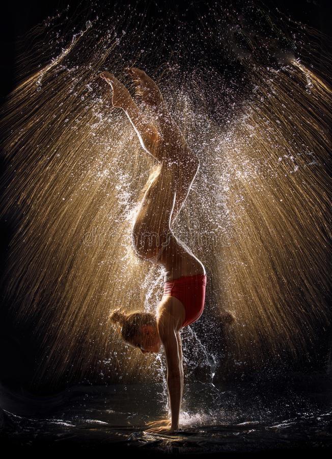 Gymnast in the spray of water royalty free stock photography