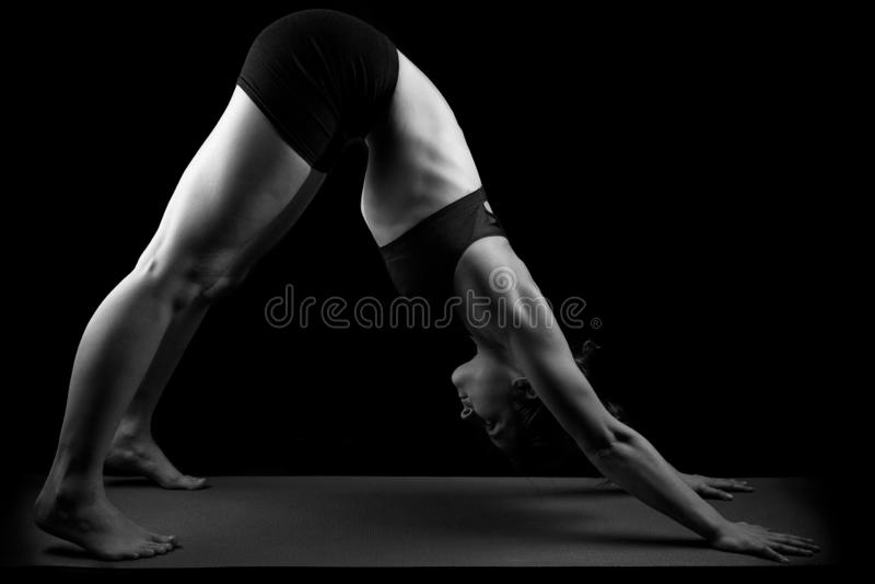 Gymnast yoga downward facing dog. Girl in gymnast outfit doing the yoga asana Adho mukha svanasana or downward facing dog on a black background royalty free stock photo