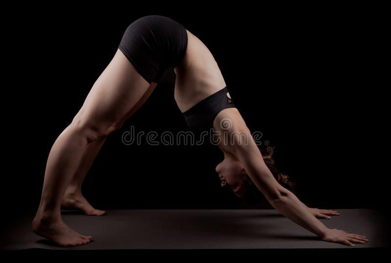 Gymnast yoga downward facing dog. Girl in gymnast outfit doing the yoga asana Adho mukha svanasana or downward facing dog on a black background in duotone stock images