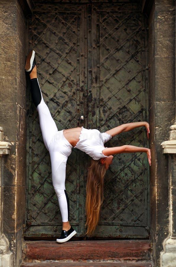 Gymnaste de fille faisant étirant des exercices sur la maison de cru photo stock