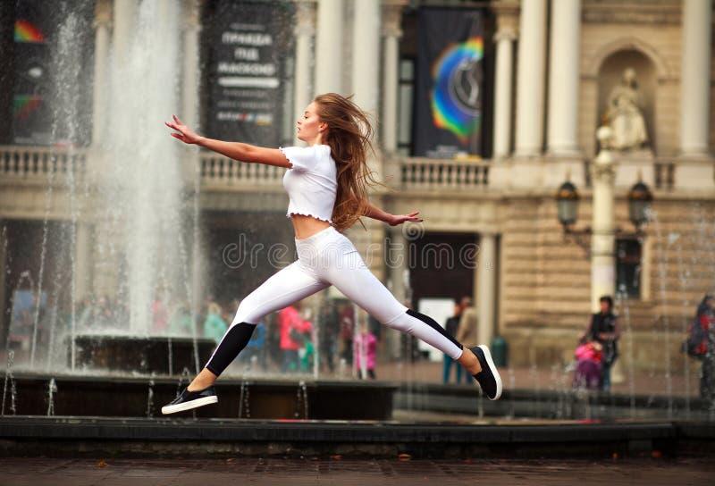 Gymnaste de fille de sports sautant en vol sur la rue de la vieille ville photo stock