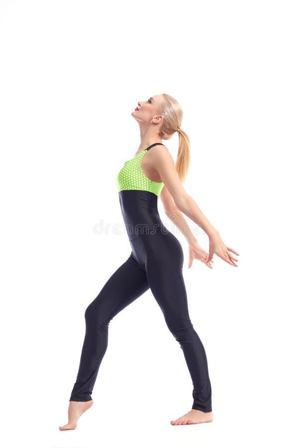 Gymnaste féminin attirant s'exerçant au studio photo stock