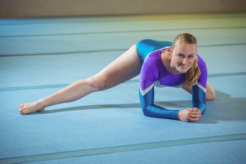 Gymnaste féminin exécutant étirant l'exercice dans le gymnase photos stock
