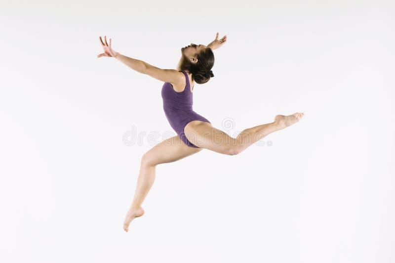 Gymnaste féminin sautant en air photos libres de droits