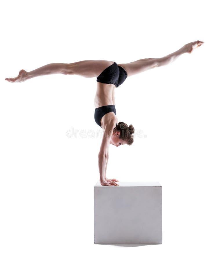 Gymnaste flexible équilibrant sur le cube dans le studio images libres de droits