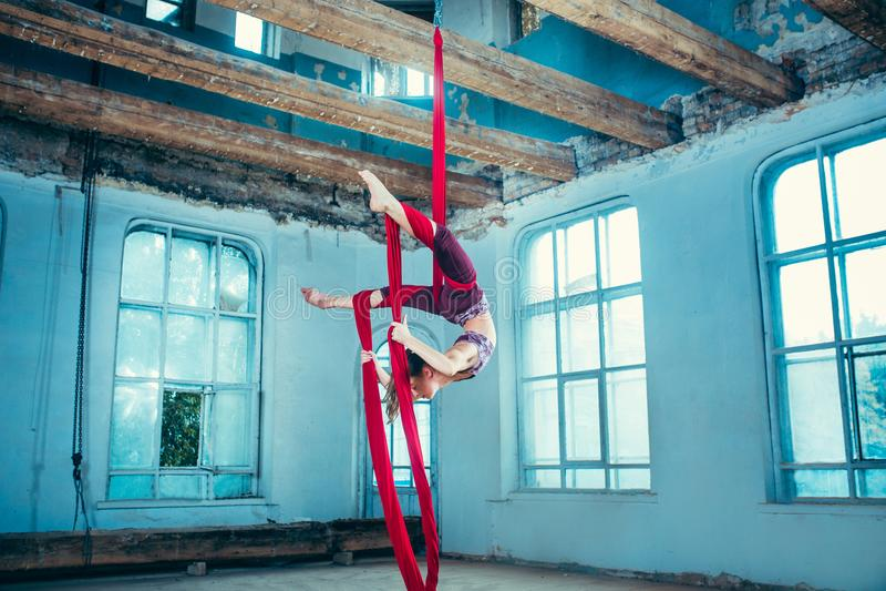 Gymnaste gracieux exécutant l'exercice aérien photo stock