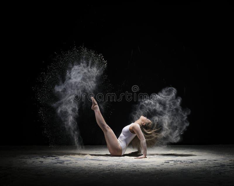 Gymnaste gracieux s'exerçant en nuage de la poussière blanche images libres de droits