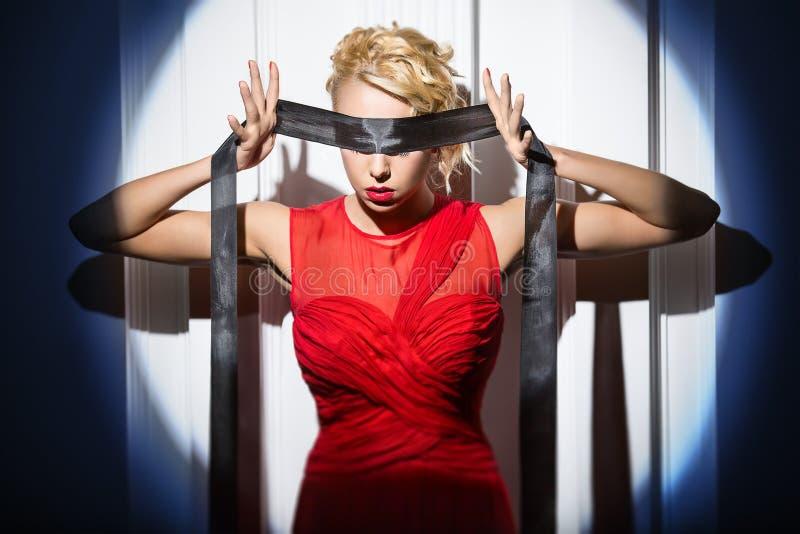 Gymnasten i den ljusa röda klänningen står med a fotografering för bildbyråer