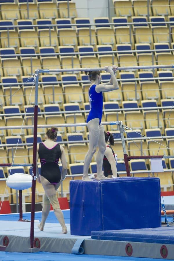 Gymnastes d'athlète de filles concurrençant dans le stade au championnat photographie stock