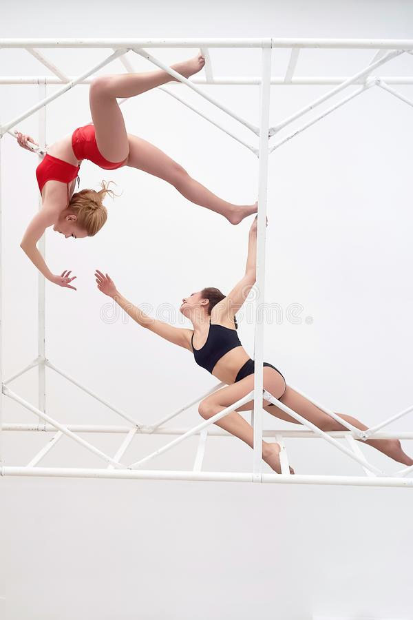 Gymnastes, paires de poses Dans le maillot de bain rouge et noir sur le fond blanc Construction ?lev?e en m?tal Corps en plastiqu photo libre de droits