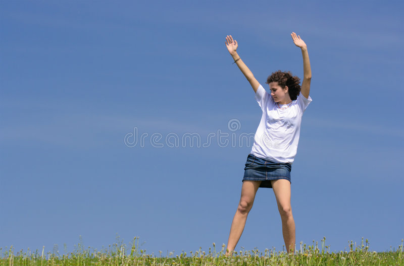 Gymnastic exercises. Teen girl to do gymnastic exercises on the grass against blue sky royalty free stock image