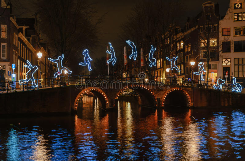 Gymnastic exercises of a light figure on a bridge. Amsterdam, Netherlands – December 18, 2015: Light Festival Amsterdam, a light figure makes a somersault stock image