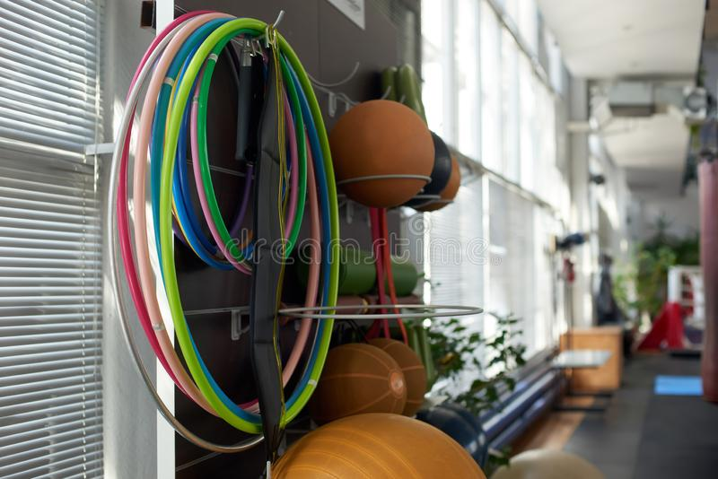 Gymnastic hoops and sport equipment at gym. Hoola hoops hanging on wall at fitness center. Interior of fitness club with training equipment royalty free stock images