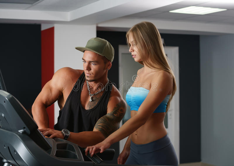 In gymnastiek De instructeur helpt meisje aan opstellingssimulator royalty-vrije stock afbeelding
