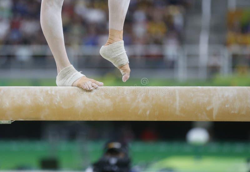 Gymnastiek jong meisje op de straal stock fotografie